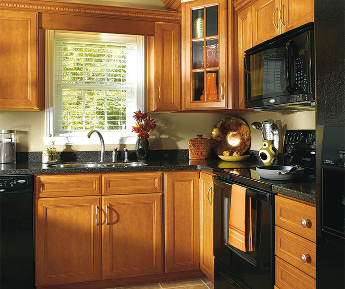 Maple wood cabinets in traditional kitchen by Aristokraft Cabinetry